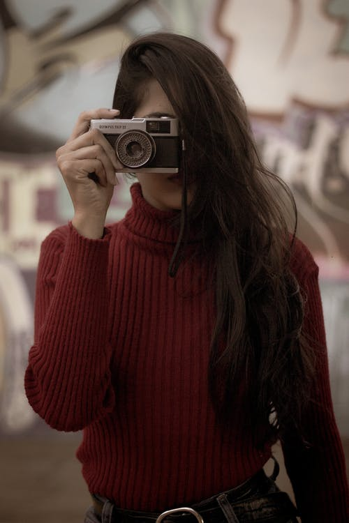 Selective Focus Photo of Woman in Red Pull-neck Sweater Holding Film Camera