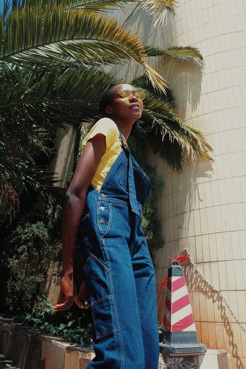 Low Angle Photo of Woman In Yellow T-shirt, Sunglasses and Blue Dungarees Posing While Looking Down