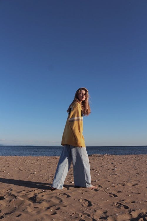 Woman Walking on Sandy Beach