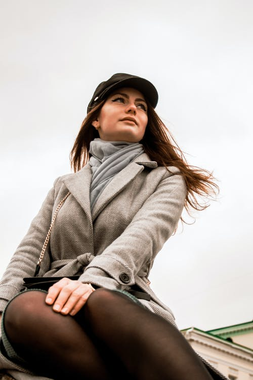 Low Angle Photo of Sitting Woman in Gray Coat and Black Hat Posing While Looking Away