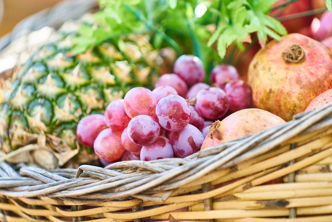 Grapes, Apple, and Pineapple on Brown Wicker Basket