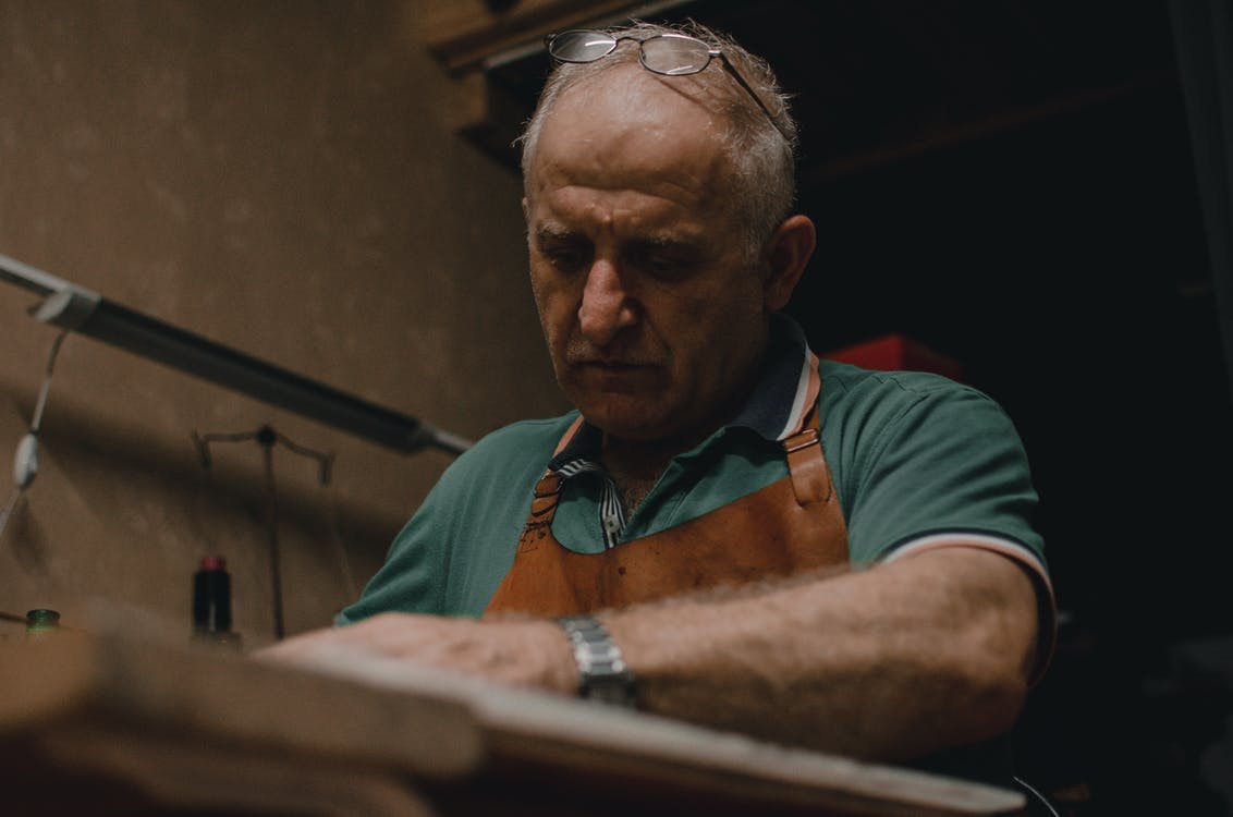 Man Wearing Brown Apron and Teal Polo Shirt