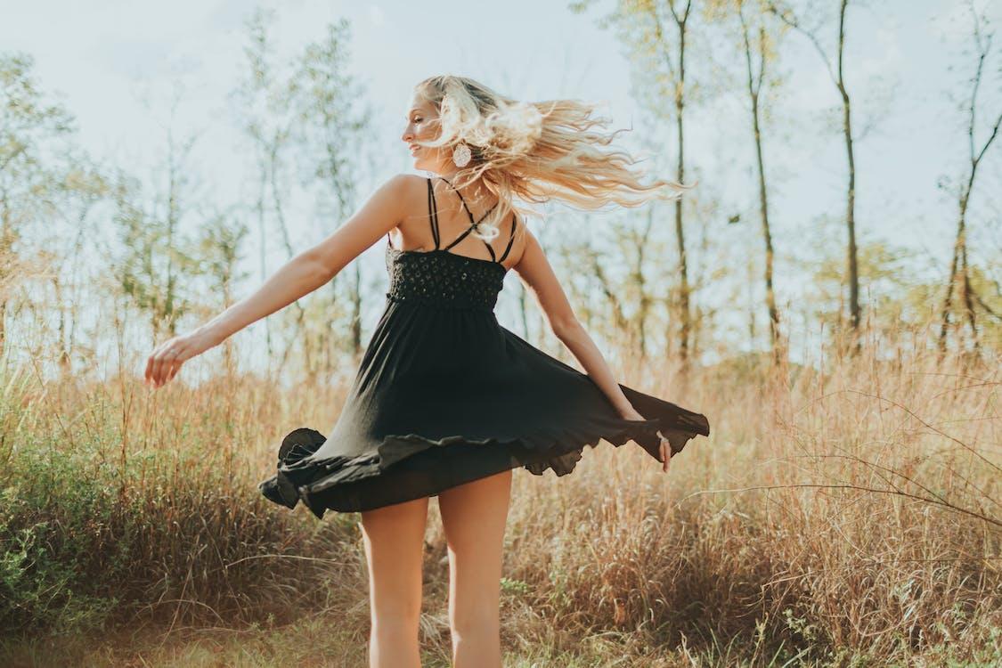 女人穿著黑色意大利麵條皮帶擺姿勢的背影照片