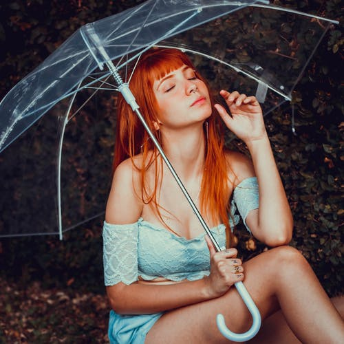 Photo of Woman Sitting While Holding a Clear Umbrella With Her Eyes Closed