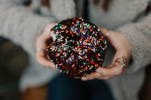 Hands Holding Chocolate Doughnut