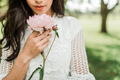 Selective Focus Photo of Woman Holding Pink Petaled Flower