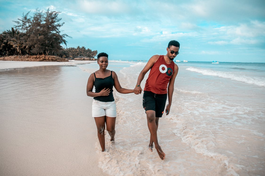 Photo of Couple Walking on Seashore While Holding Hands