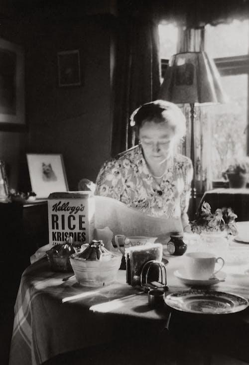 Grayscale Photo of Woman Having Breakfast