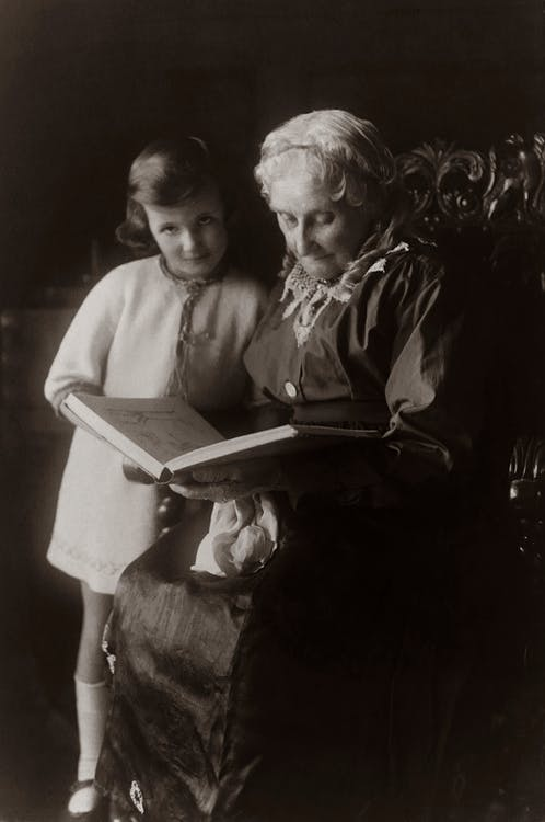 Old Woman Sitting on Chair Near Girl While Reading A Book