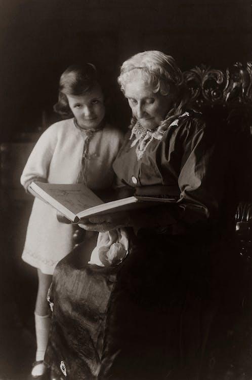 Anciana Sentada En Una Silla Junto A La Niña Mientras Lee Un Libro