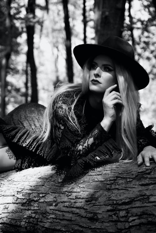 Grayscale Photo of Woman in Hat and Dress Lying Down on Log Posing