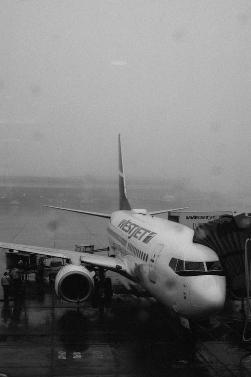 Grayscale Photography Of An Airplane On Tarmac