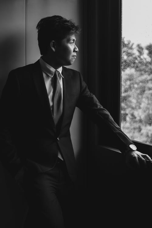 Greyscale Photography of Man Wears Suits Near the Window