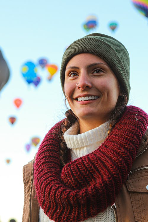 Smiling Woman Wearing Gray Beanie Cap and Red Scarf