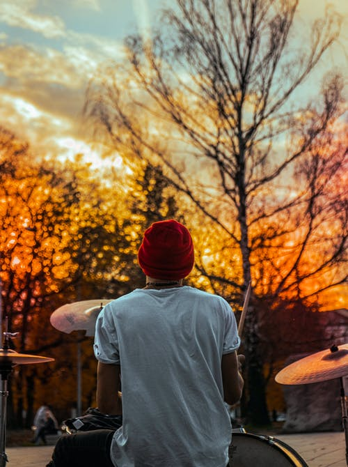 Back View Photo of Man Playing Drums During Golden Hour