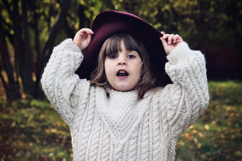 Selective Focus of Small Girl in Maroon Hat and White Knitted Sweater Posing