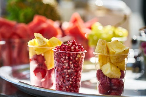 Close-Up Photo Of Sliced Fruits On Plastic Cup