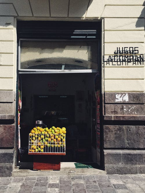 A Container With Piled Green Fruit On The Doorway Of A Building