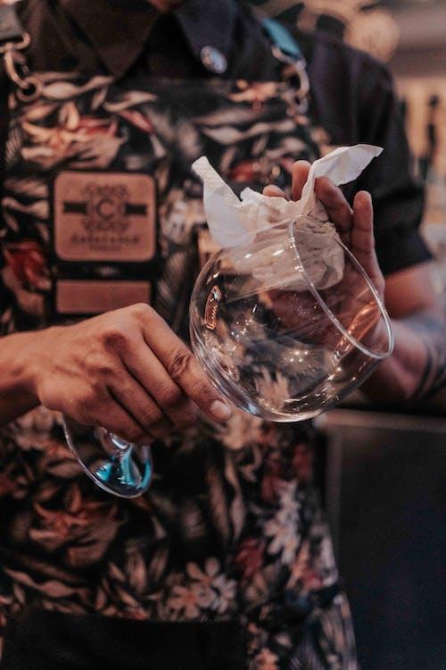 Человек, протирающий бокал для вина
