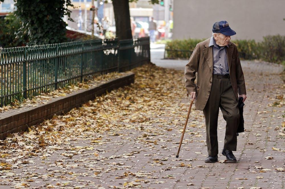 Elderly man walking on pavement.   Photo: Pexels