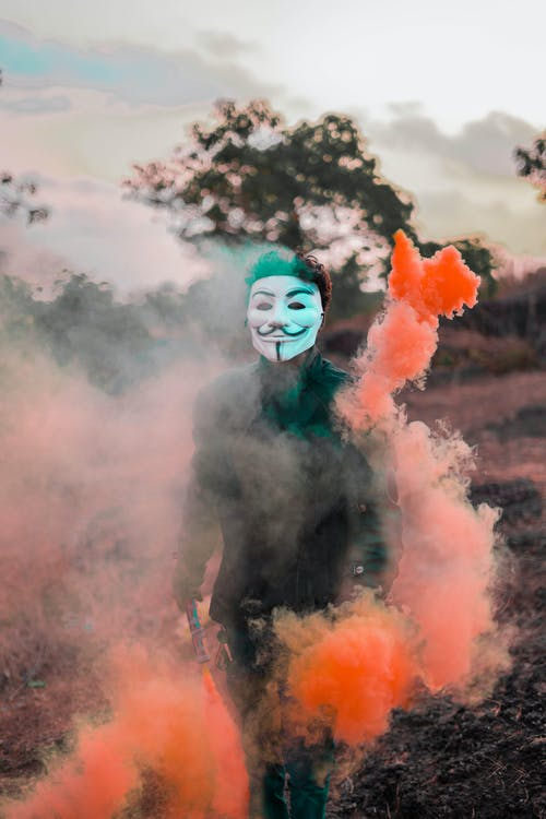 Person Wearing Guy Fawkes Mask Surrounded With Colored Smoke