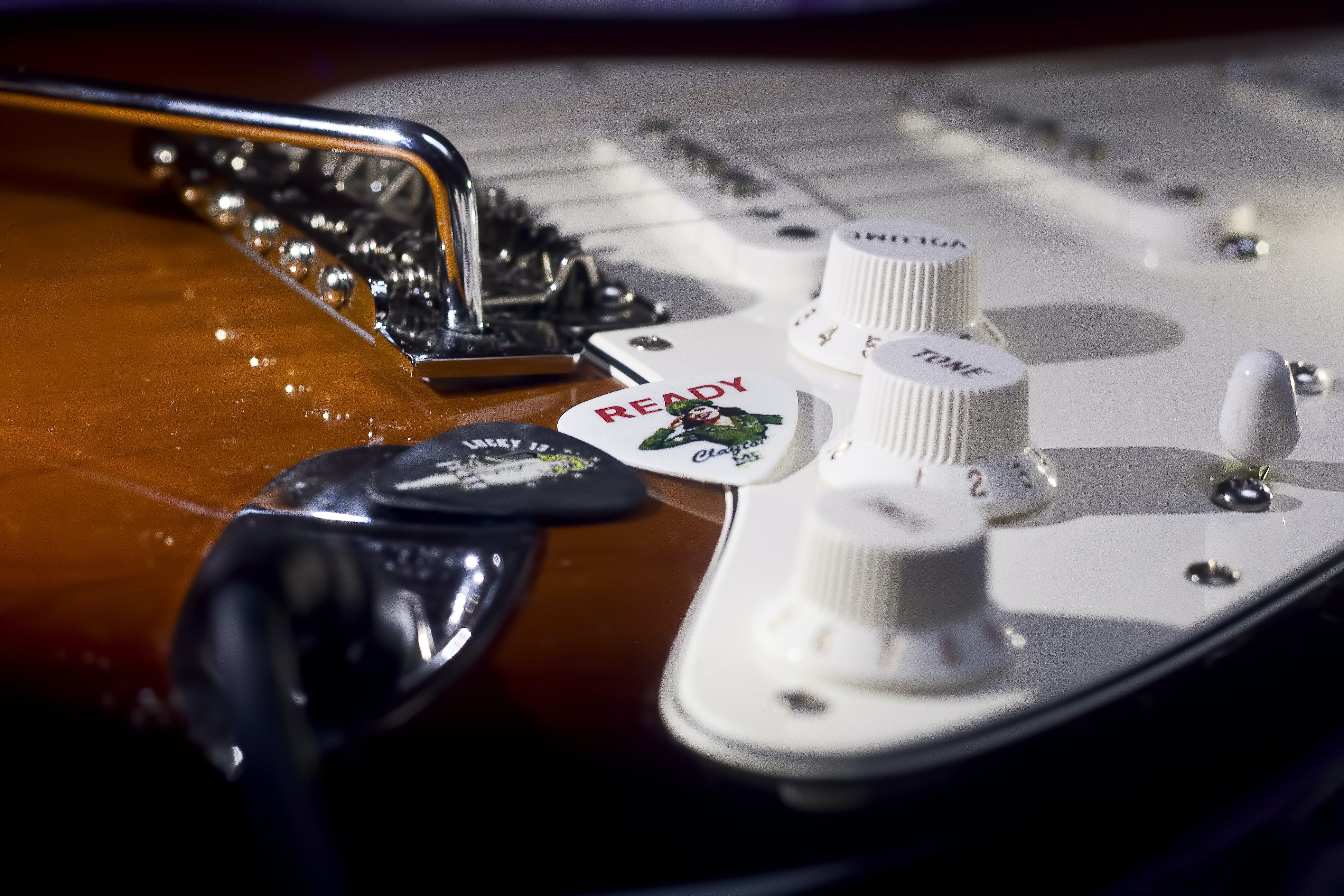 Selective Focus Photo of Brown and White Electric Guitar