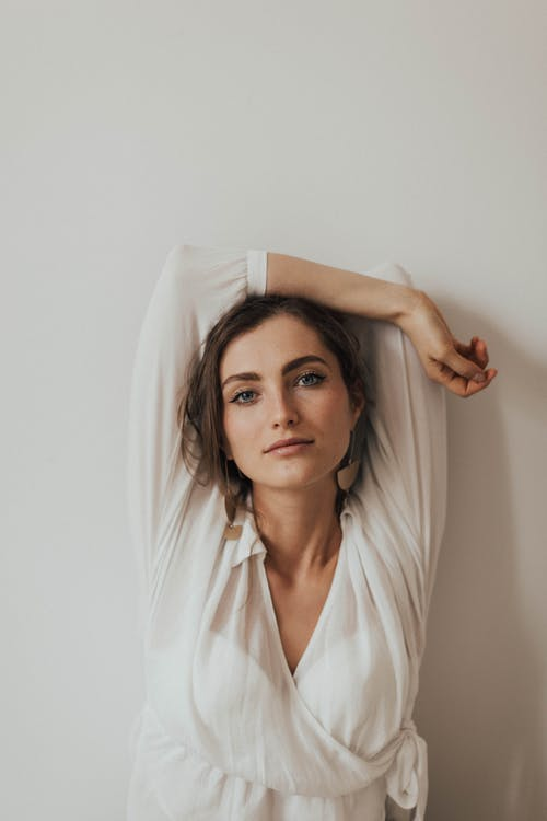 Photo of Woman in White V-neck Long-sleeved Blouse Posing by White Wall With her Hand Over Her Head
