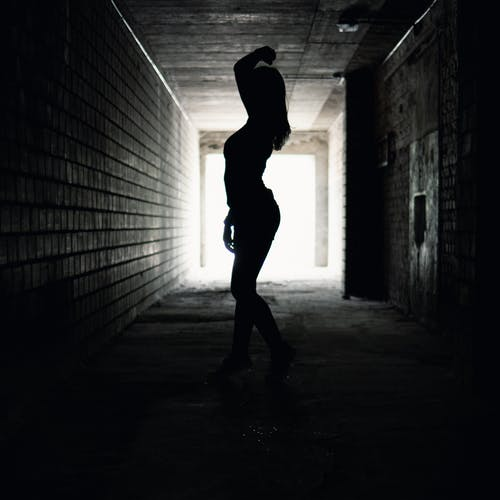 Silhouette Photo of Person Standing in Tunnel