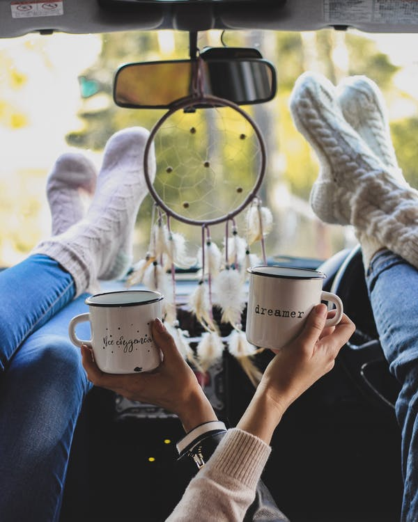 Two People Holding Coffee Mugs With Their Feet On The Dashboard Of A Vehicle With An Ornament Hanging On The Rear View Mirror
