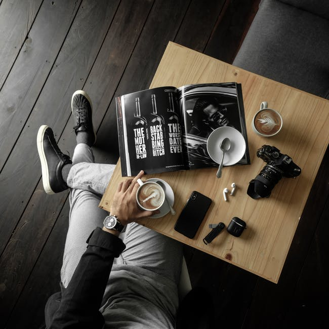 Top view of a table with man holding a cup of latte with a magazine camera cellphone and other perso...