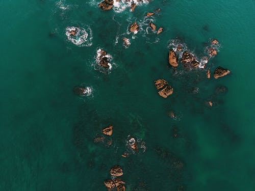 Top View Photo of Rock Formations on Water