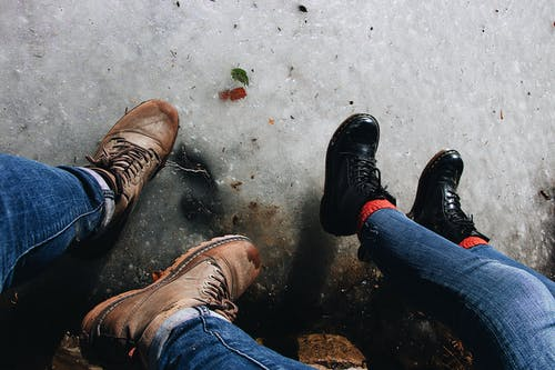 High Angle Photo of Two Person Wearing Leather Boots