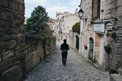 Photo of Person Walking on Cobblestreet