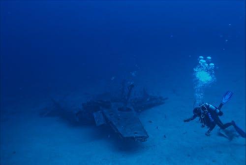 Anonymous diver swimming near sunken plane