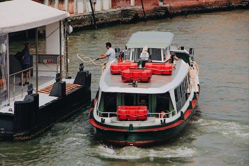 Man mooring motor boat near pier