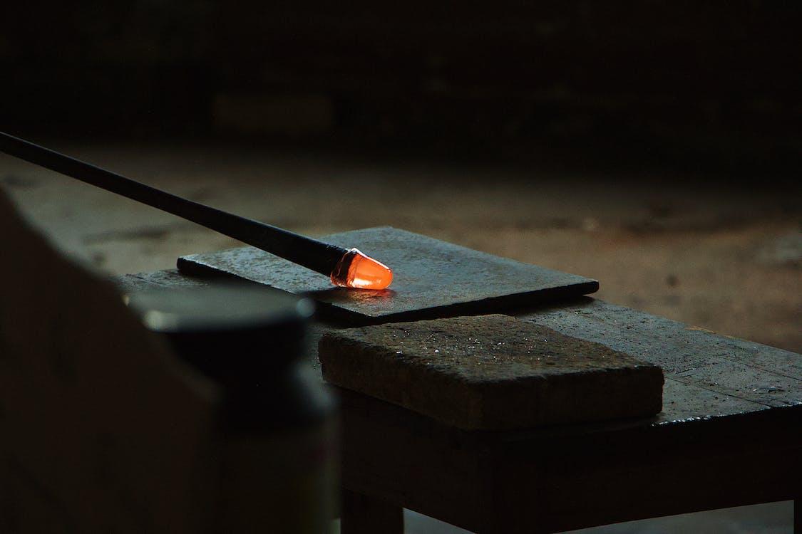 Glassblowing pipe in dark workshop