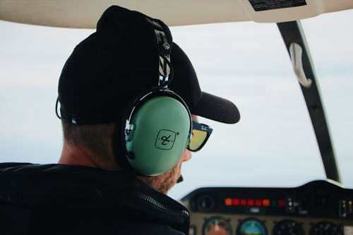 Close-up Of A Man Wearing A Headphone And Sunglasses Inside An Aircraft Cockpit