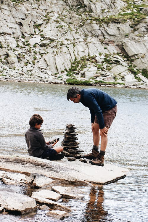 Man And Boy Stacking Stones