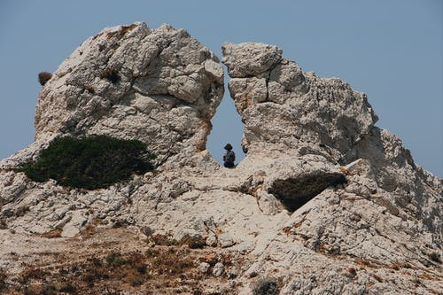 Woman Sitting On A Hole In The Middle Of A Huge Rock Formation