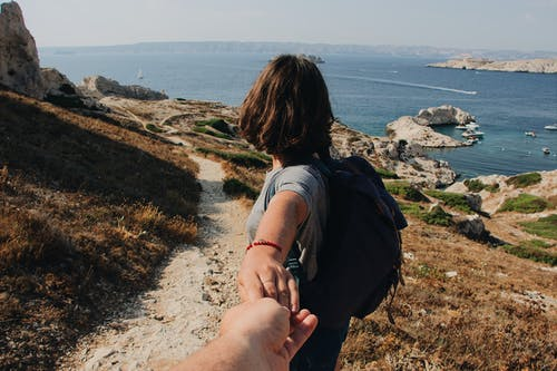 Photo of Couple Holding Hands While Standing Outdoors