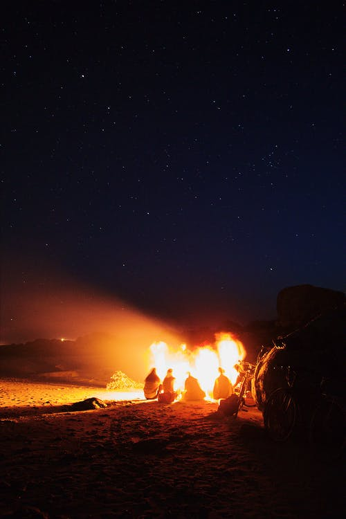 People Gathered Around A Bonfire Outdoors Under Starry  Night Sky