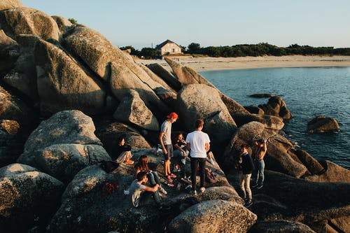 A Group Of Young People Lazing Around The Boulders By The Sea Close To The Shoreline
