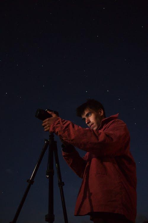 Hombre Vestido Con Chaqueta Roja De Pie Junto A La Cámara Con Trípode Durante La Noche