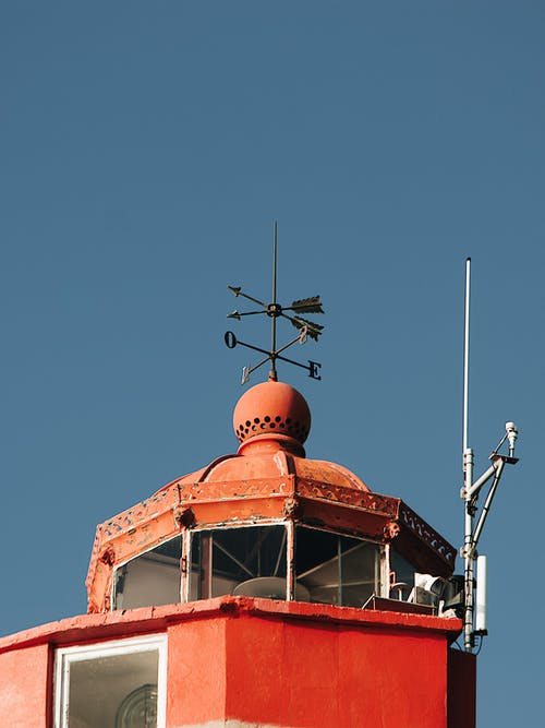 Low Angle Shot Of A Wind Vane And A Antenna On Top Of A Lighthouse