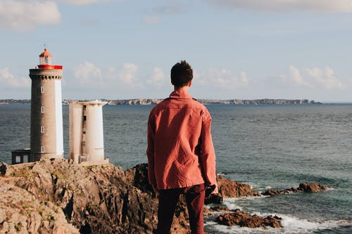 Back view of unrecognizable male traveler in casual red clothes contemplating seascape while standing on rocky shore with lighthouse near rippling sea