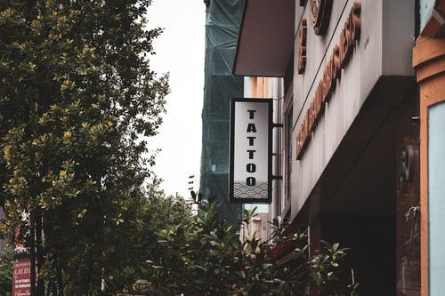 """建筑物前的绿树,外面挂着""""纹身""""标牌"""