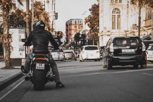 Man Wearing Jacket and Pants Riding On Motorcycle