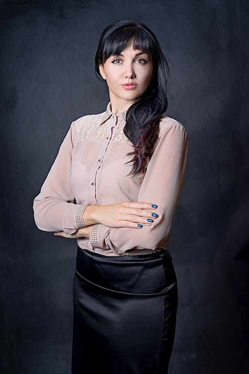 Woman In a Black Skirt and Beige Blouse Posing