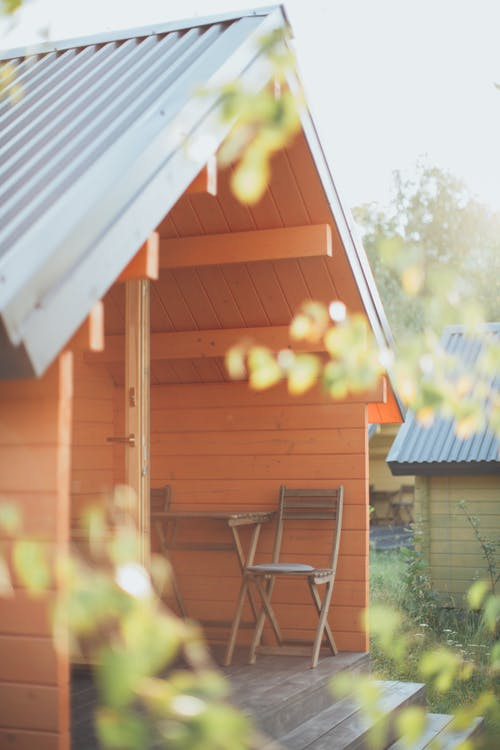 Chair Beside Table  In Front Of An Orange Wooden Shed