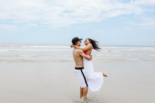 Photo of Happy Couple Hugging on the Beach